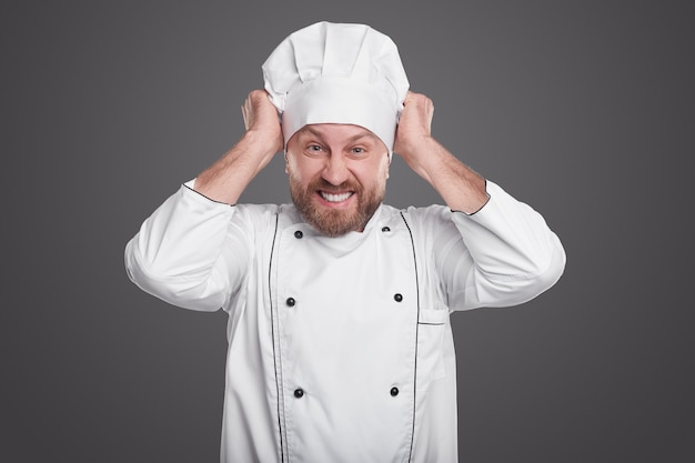 Wütender bärtiger männlicher koch, der kamera betrachtet und hut im zorn zieht, während im restaurant gegen grauen hintergrund arbeitet