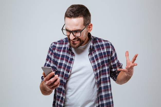 Wütender bärtiger mann in den augen, die telefon betrachten