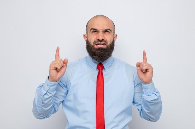 Wütender bärtiger mann in roter krawatte und blauem hemd, der aufschaut und mit den zeigefingern nach oben zeigt
