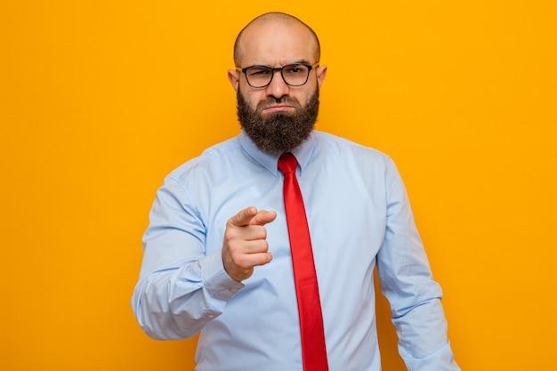 Wütender bärtiger mann in roter krawatte und hemd mit brille, der mit dem zeigefinger auf die kamera zeigt, mit ernstem gesicht auf orangefarbenem hintergrund