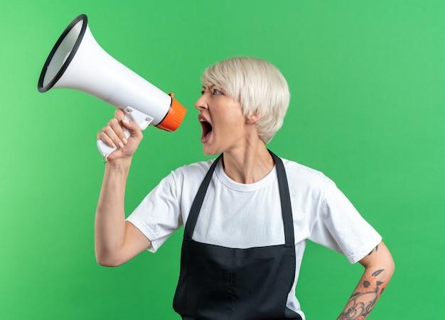 Wütender blick auf die junge schöne friseurin in uniform spricht über lautsprecher isoliert auf grüner wand