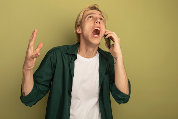 Wütender blick nach oben junger blonder kerl, der grünes t-shirt trägt, spricht am telefon, das hand hebt
