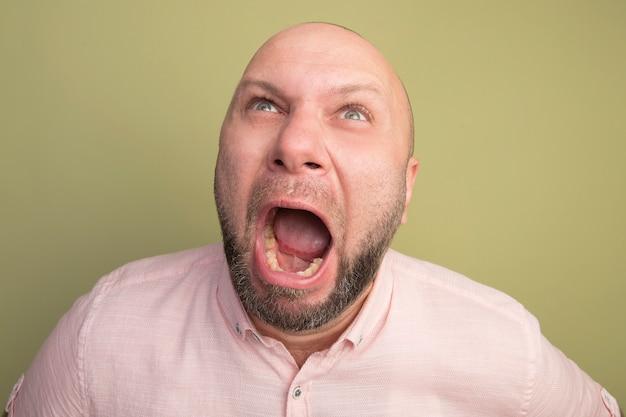 Wütender blick nach oben kahler mann mittleren alters, der rosa t-shirt trägt