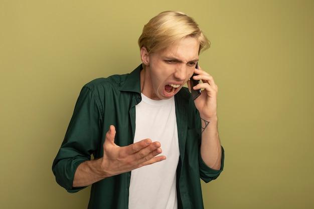 Wütender blick nach unten junger blonder kerl, der grünes t-shirt trägt, spricht am telefon