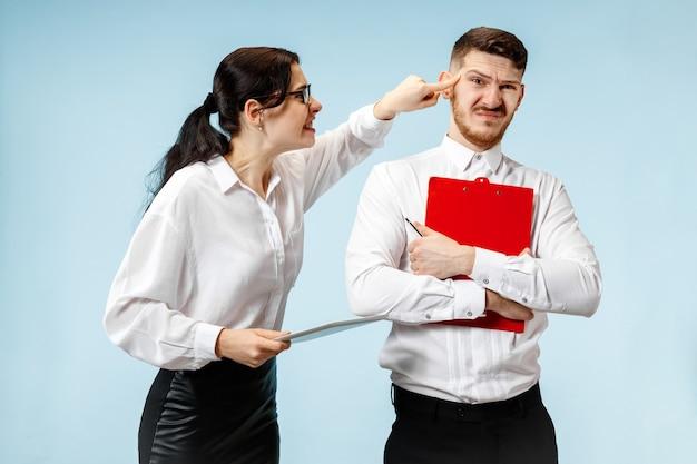 Wütender chef. frau und seine sekretärin stehen im büro oder im studio. geschäftsfrau schreit zu seinem kollegen. weibliche und männliche kaukasische modelle. bürobeziehungskonzept, menschliche emotionen