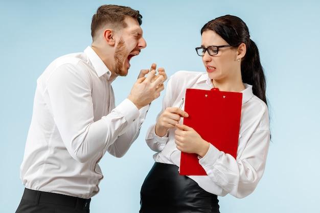 Wütender chef. mann und seine sekretärin stehen im büro oder im studio. geschäftsmann schreit zu seinem kollegen. weibliche und männliche kaukasische modelle. bürobeziehungskonzept, menschliche emotionen