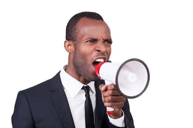 Wütender chef. wütender junger afrikaner in abendgarderobe schreit megaphon an, während er isoliert auf weißem hintergrund steht