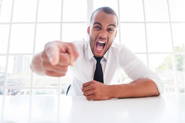 Wütender chef. wütender junger afrikaner in hemd und krawatte, der auf dich zeigt und schreit