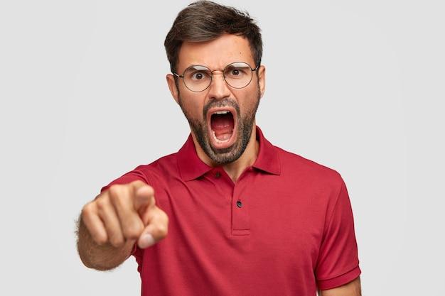 Wütender depressiver mann mit dunklen borsten, schreit jemanden wütend an, zeigt auf ein rotes t-shirt, das über einer weißen wand isoliert ist. unrasierter verrückter drückt wut aus, schreit laut