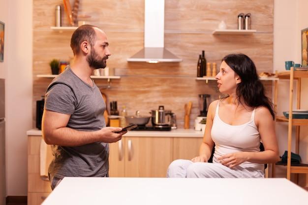 Wütender ehemann konfrontiert betrügerische ehefrau wegen untreue, während er ihr telefon hält. frustriert beleidigt irritiert beschuldigt frau der untreue, die sie beschuldigt.