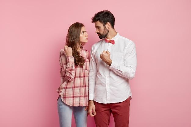 Wütender ehemann und ehefrau sehen sich streng an, zeigen fäuste, streiten sich, tragen ein stilvolles outfit, klären beziehungen