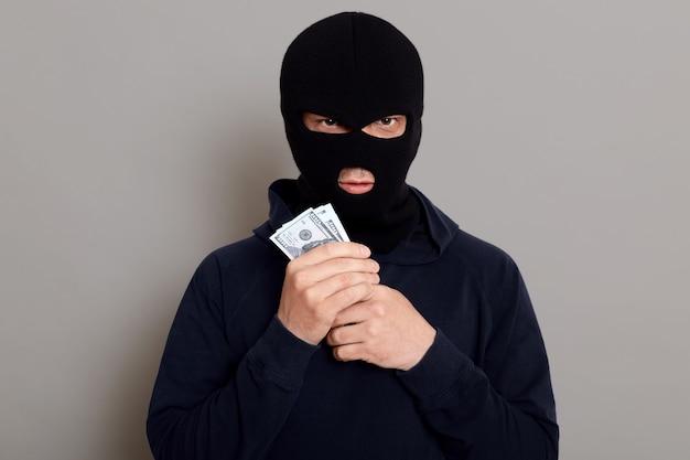 Wütender einbrecher schaut mit gefälschtem gesichtsausdruck nach vorne und hält das gestohlene geld in seinen händen