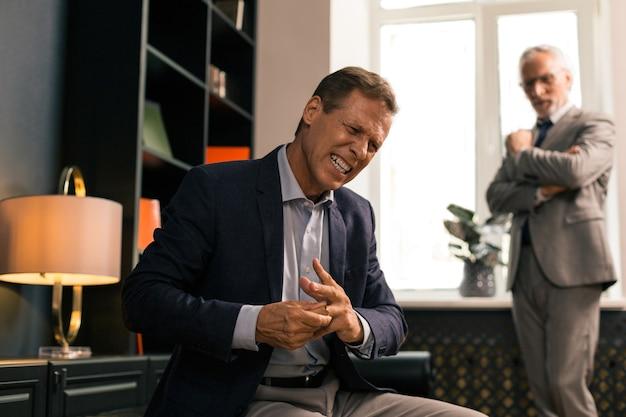 Wütender enttäuschter mann, der seinen ehering abnimmt, während er in seinem büro als psychoanalytiker sitzt