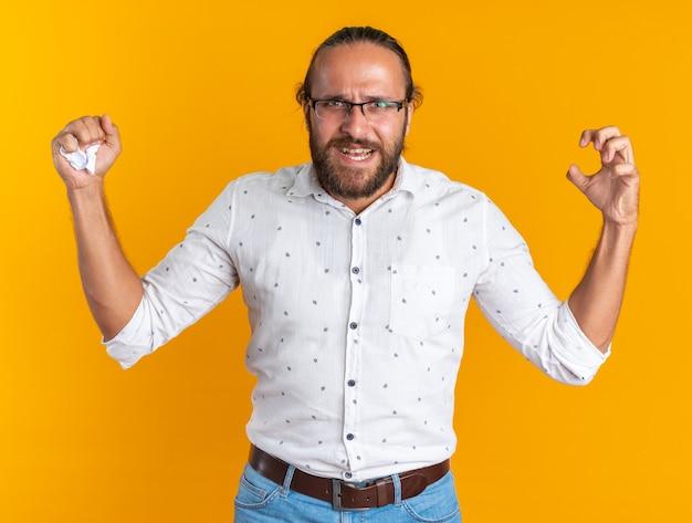 Wütender erwachsener gutaussehender mann mit brille, der die hand in der luft hält, die papier in der hand zerkleinert