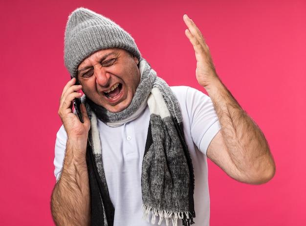 Wütender erwachsener kranker kaukasischer mann mit schal um den hals mit wintermütze, der jemanden am telefon anschreit, isoliert auf rosa wand mit kopierraum
