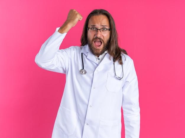 Wütender erwachsener männlicher arzt, der ein medizinisches gewand und ein stethoskop mit brille trägt und in die kamera schaut, die die faust isoliert auf rosa wand hebt