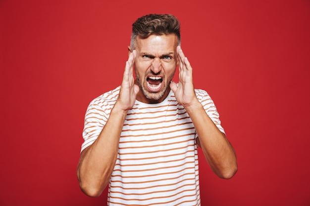 Wütender erwachsener mann im gestreiften t-shirt schreit und berührt das gesicht isoliert auf rot
