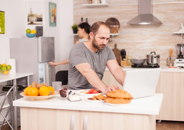 Wütender freiberufler, der von zu hause aus am küchentisch sitzt, während seine frau das frühstück zubereitet. unglücklicher, gestresster, frustrierter wütender negativer und verärgerter freiberufler im pyjama, der während des morgens schreit