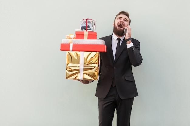 Wütender geschäftsmann, der geschenkbox hält und am telefon schreit