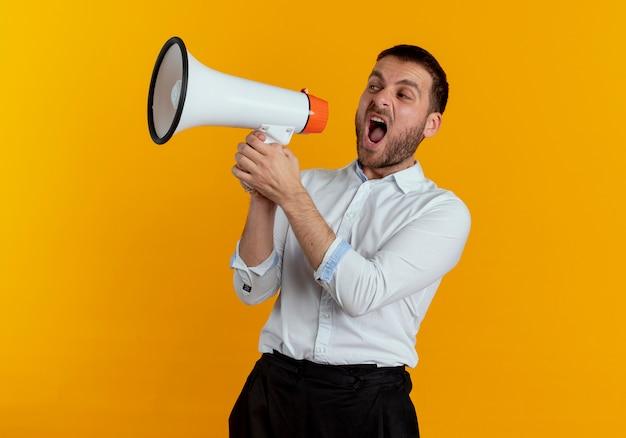 Wütender gutaussehender mann schreit in lautsprecher, der seite betrachtet, die auf orange wand lokalisiert ist