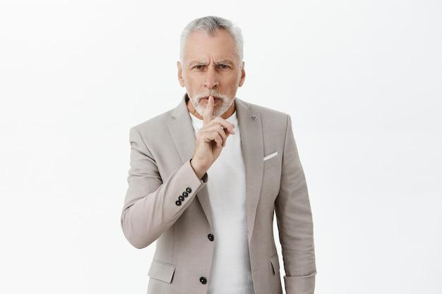 Wütender herrischer alter mann mit grauem haar, das zum schweigen gebracht wird, finger an die lippen drücken, sagen, sei ruhig