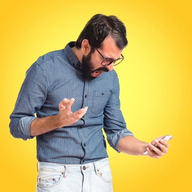 Wütender hipstermann, der mit dem mobile auf buntem hintergrund spricht