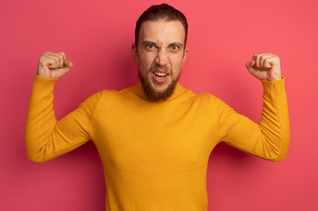 Wütender hübscher blonder mann hält fäuste auf rosa