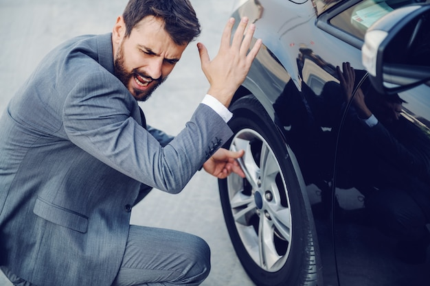 Wütender hübscher kaukasischer geschäftsmann, der neben seinem auto hockt, schreit und flucht. platter reifen.