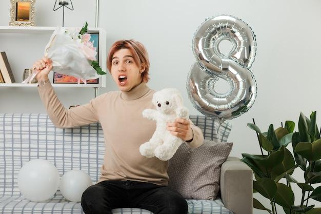 Wütender hübscher kerl am glücklichen frauentag, der blumenstrauß mit teddybär hält, der auf sofa im wohnzimmer sitzt