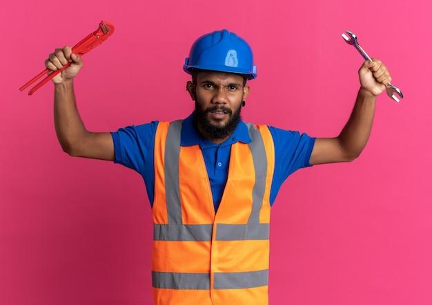 Wütender junger baumeister in uniform mit schutzhelm mit werkstattschlüssel und rohrzange isoliert auf rosa wand mit kopierraum