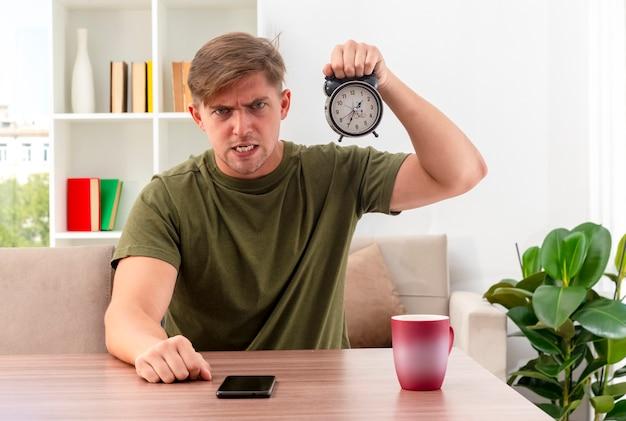 Wütender junger blonder hübscher mann sitzt am tisch mit tasse und telefon, die wecker halten und kamera im wohnzimmer betrachten
