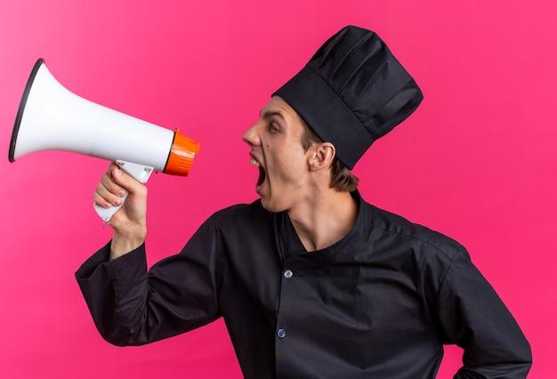 Wütender junger blonder männlicher koch in kochuniform und mütze, der auf die seite schreit, die im lautsprecher isoliert auf rosa wand schreit?