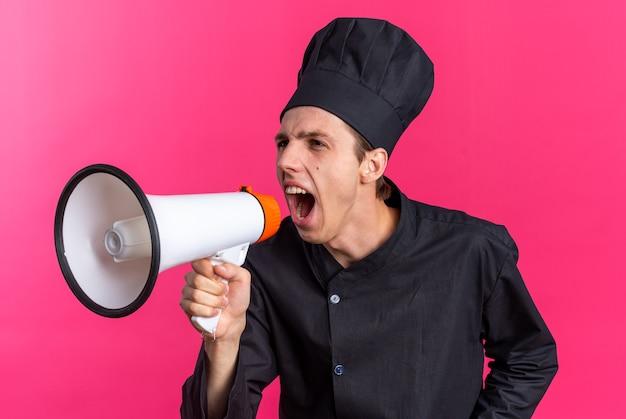 Wütender junger blonder männlicher koch in kochuniform und mütze, der seitlich im lautsprecher schreit loud