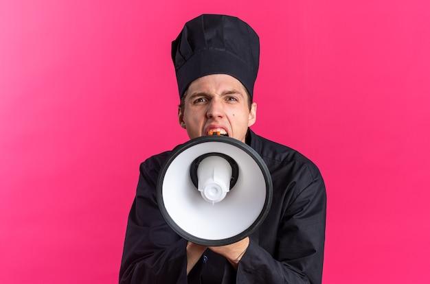 Wütender junger blonder männlicher koch in kochuniform und mütze schreit im lautsprecher