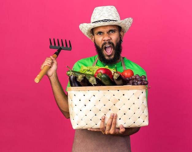 Wütender junger gärtner afroamerikanischer mann mit gartenhut, der gemüsekorb mit rechen hält