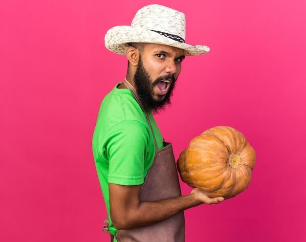 Wütender junger gärtner afroamerikanischer mann mit gartenhut mit kürbis