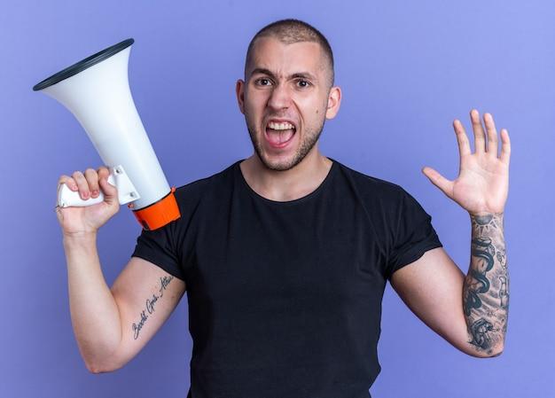 Wütender junger gutaussehender kerl mit schwarzem t-shirt mit lautsprecher auf blauem hintergrund