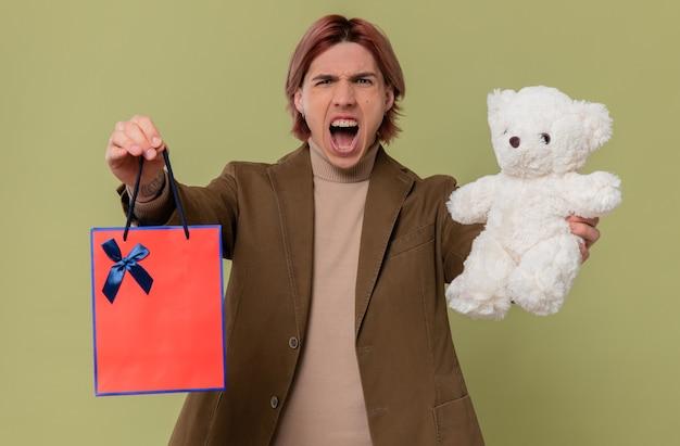Wütender junger gutaussehender mann mit weißem teddybär und geschenktüte, der jemanden anschreit
