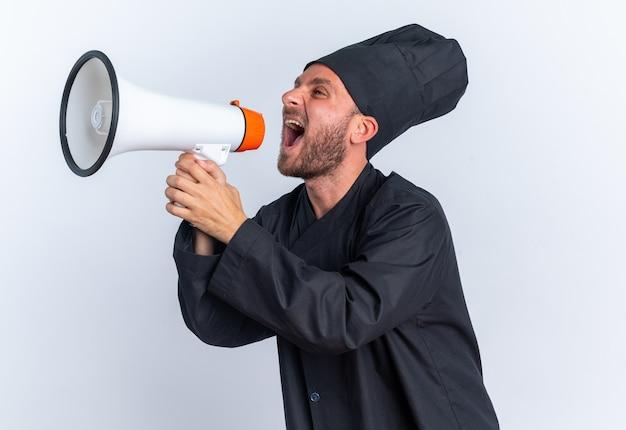 Wütender junger kaukasischer männlicher koch in kochuniform und mütze, der in der profilansicht steht und seitlich im lautsprecher schreit