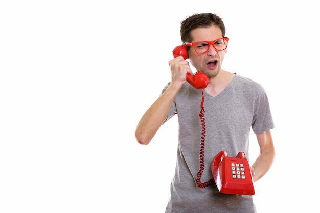 Wütender junger mann, der am alten telefon spricht