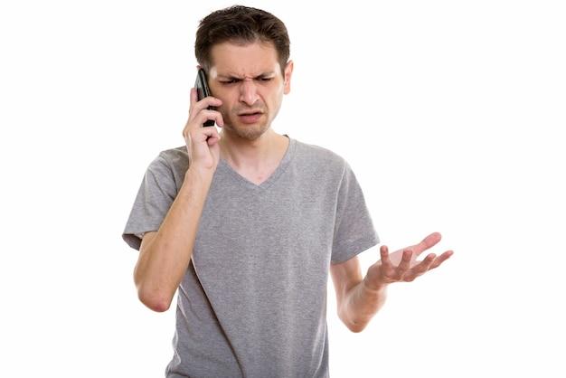Wütender junger mann, der auf handy spricht