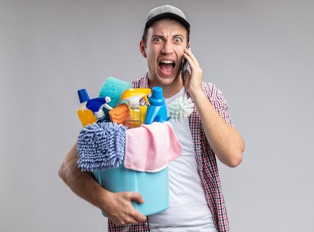 Wütender junger mann, der eine mütze trägt, die einen eimer mit reinigungswerkzeugen hält, spricht am telefon isoliert auf weißer wand