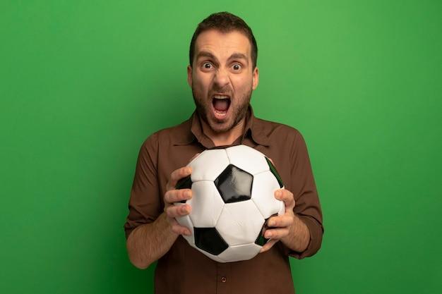 Wütender junger mann, der fußball hält, der front schreit, lokalisiert auf grüner wand