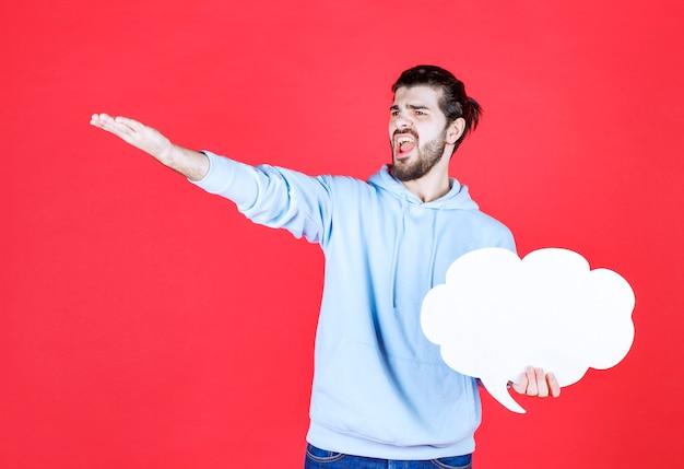 Wütender junger mann, der ideentafel in wolkenform hält und mit dem finger zur seite zeigt