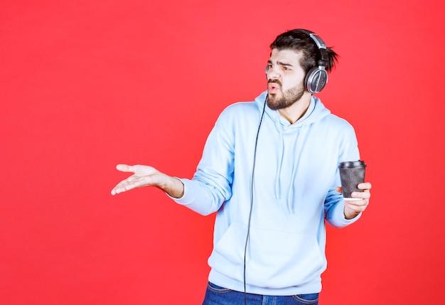 Wütender junger mann, der kaffeetasse hält und musik hört