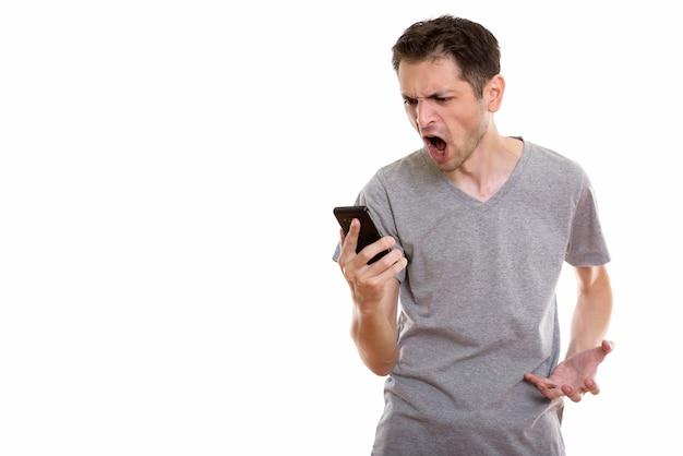 Wütender junger mann, der schreit, während er handy benutzt