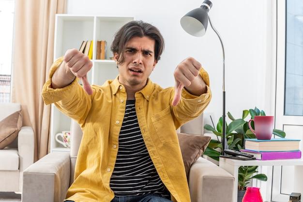 Wütender junger mann in freizeitkleidung mit daumen nach unten auf dem stuhl im hellen wohnzimmer sitzend