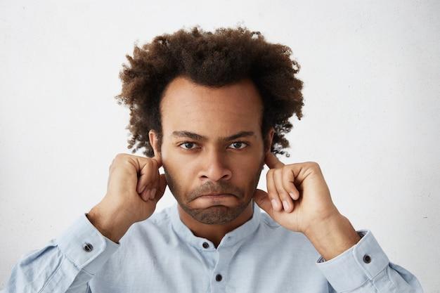 Wütender junger mann irritiert von lautem geräusch