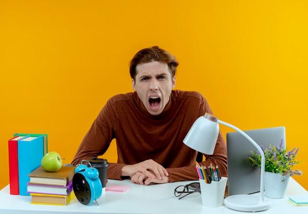 Wütender junger studentjunge, der mit schulwerkzeugen am schreibtisch sitzt
