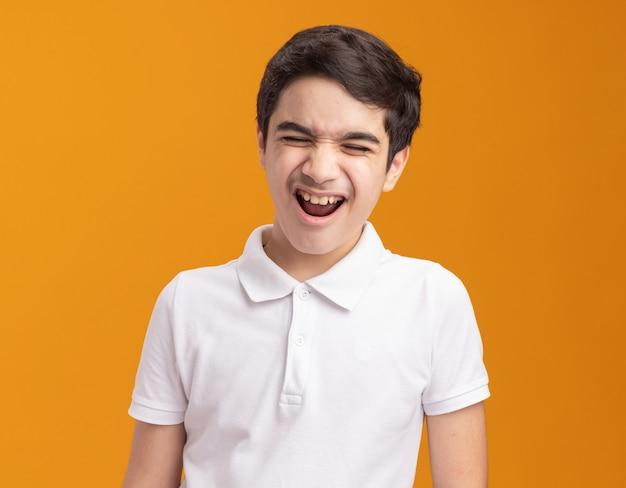 Wütender kleiner junge, der mit geschlossenen augen schreit, isoliert auf oranger wand